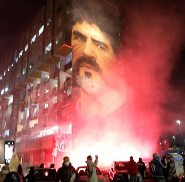 Fan Napoli thắp pháo sáng bên bức tường in gương mặt Cậu bé vàng. Tất cả các trường học ở Naples sẽ được nghỉ ngày 26/11 để tưởng nhớ Maradona