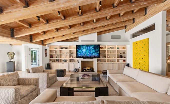 Nội thất được thiết kế theo phong cách hiện đại, sang trọng và thanh lịch. Ngôi nhà gây ấn tượng với trần dầm gỗ gắn đèn sân khấu tạo không gian lung linh và ấm cúng về đêm.