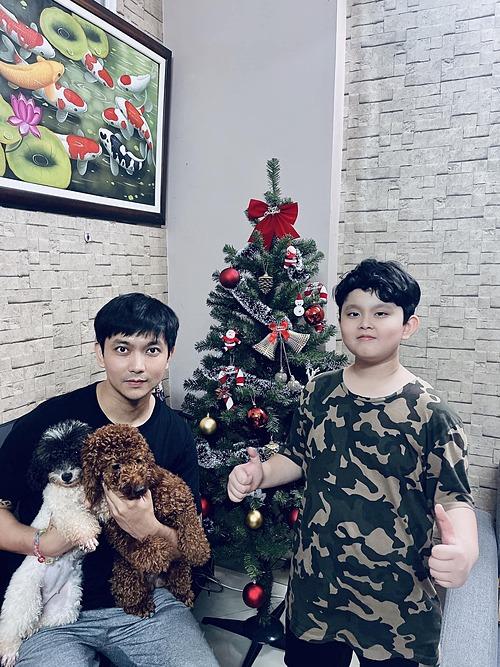 Ca sĩ Tim và con trai pose ảnh bên cây thông Noel.