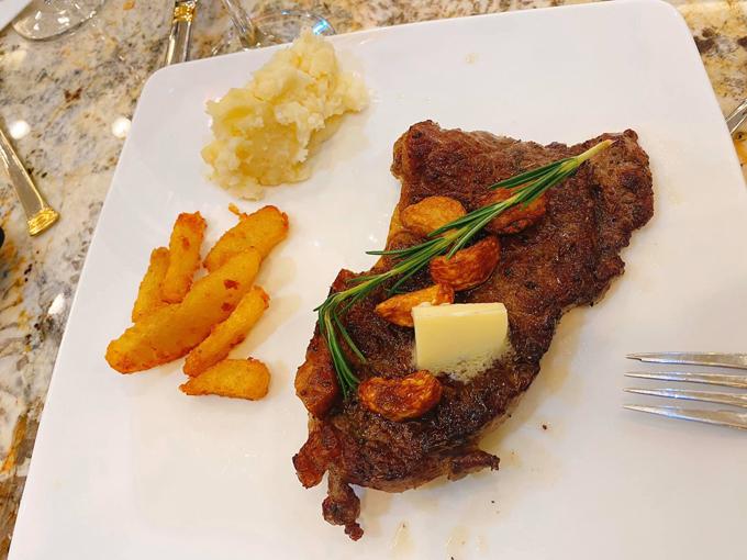 Món bò bít tết của hot mom được trình bày giống ngoài hàng, có một miếng bơ giúp thịt có mùi thơm, lá rosemary và tỏi làm nâng hương vị món ăn. Bên cạnh là chút khoai tây nghiền và khoai tây chiên.