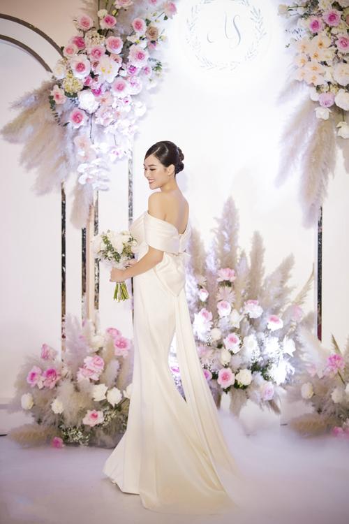 Điều đặc biệt là Tường San quyết định chọn màu ngọc trai thay vì màu trắng tinh cho thiết kế đón khách, mang lại dáng vẻ cổ điển và sang trọng. Mặt sau của lưng váy có nơ to bản làm tà phụ dài, giúp từng nhịp bước của cô dâu uyển chuyển.
