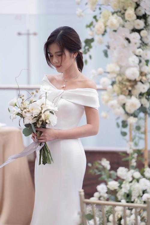 Cổ váy được tạo hình một chiếc nơ với những đường xếp nếp mềm mại, điệu đà. Thiết kế trễ vai này che được khuyết điểm bắp tay to cho các nàng dâu, đồng thời tạo điểm nhấn hút mắt vào bờ vai thon.