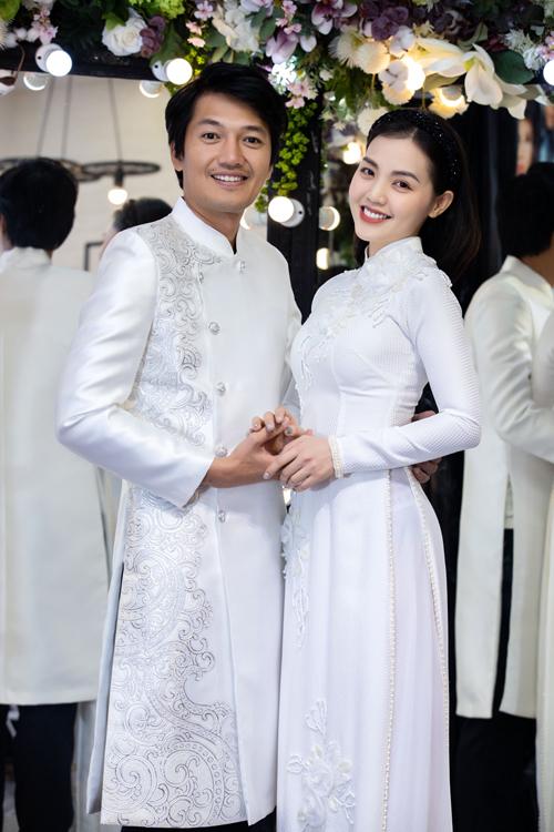 Vợ chồng Linh Phi - Quang Tuấn cùng diện áo dài trắng, bồi hồi nhớ lại cảm xúc ngày cưới năm xưa. Do cả hai có vóc dáng chuẩn nên dễ dàng chinh phục áo dài ôm dáng của Minh Châu.