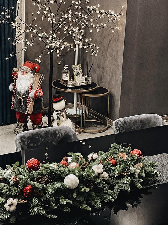 Mỗi góc trong nhà đều được tô điểm bằng ông già Noel, người tuyết... Bàn ăn cũng được trang trí bằng lá thông, quả châu đồng điệu với phong cách nội thất.