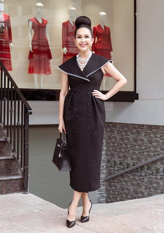 Nữ hoàng ảnh lịch phối trang phục cùng bông tai và vòng cổ ngọc trai Chanel, túi xách Hermes Kelly đắt đỏ.