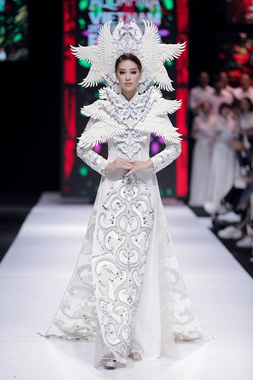 Hoa hậu Hoàn vũ Việt Nam Khánh Vân xuất hiện trong vai trò kết màn. Cô cũng diện áo dài trắng kín đáo với điểm nhấn là hoạ tiết chim phượng nổi bật. Các chi tiết thêu cầu kỳ làm toát lên vẻ sang trọng, quyền lực của bộ cánh.