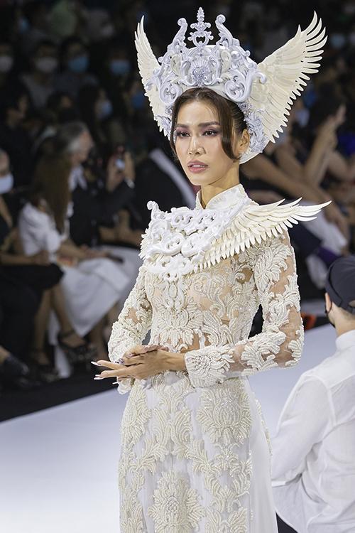 Hoa hậu siêu quốc gia Việt Nam sải bước trong áo dài ren, ôm giúp khoe dáng thon, đường cong nữ tính. Sự kết hợp hai yếu tố truyền thống, hiện đại trên cùng một bộ trang phục giúp áo dài tiếp cận gần gũi với người yêu thích thời trang.