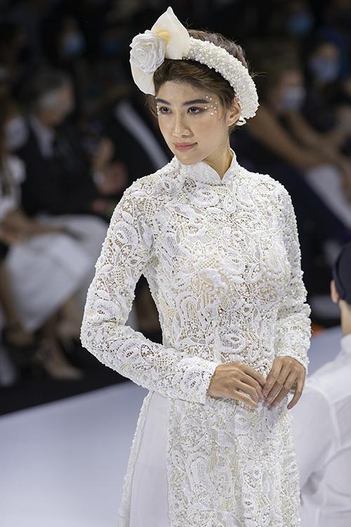 Áo dài ren cũng là thế mạnh mà Minh Châu khai thác cho bộ sưu tập lần này. Anh chọn lựa đính kết các loại hạt ngọc bắt sáng dọc thân, khiến cho cô dâu nổi bật khi sải bước.