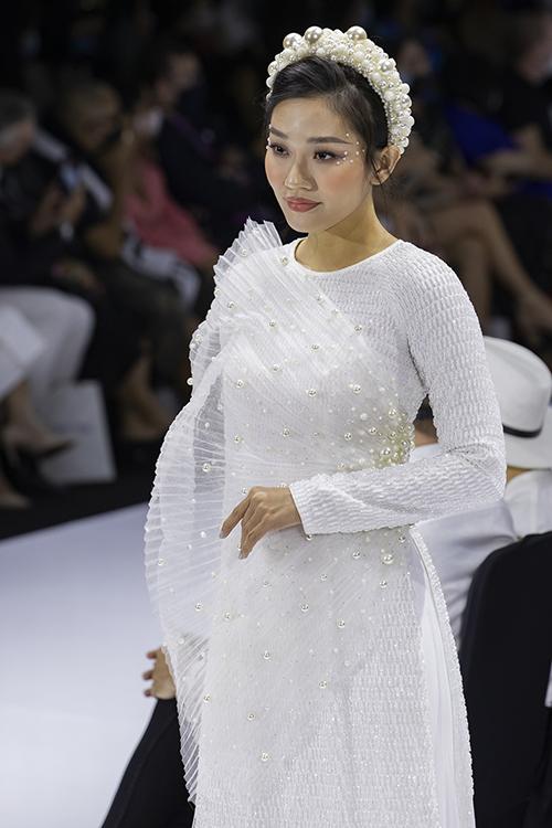 Áo dài cách điệu với vải có cấu trúc bề mặt đặc biệt, đính thêm miếng vải tạo hình cùng hạt ngọc trai mang đến nét hiện đại.