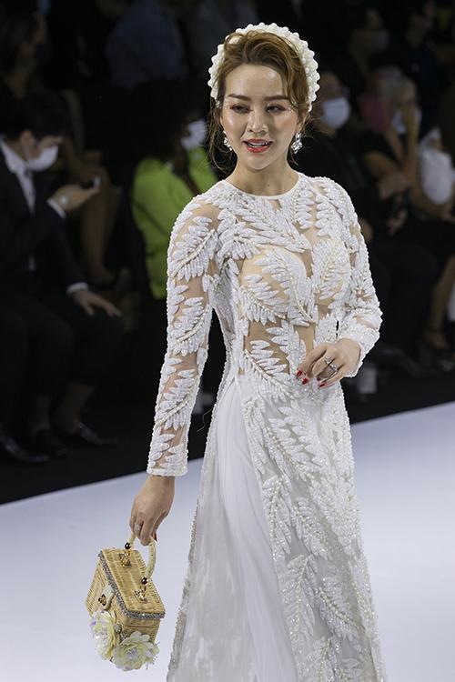 Minh Châu đem đến áo dài xuyên thấu hoạ tiết lông vũ. Bộ cánh bắt sáng vì đã được điểm các hạt đá dày đặc trên hoạ tiết.