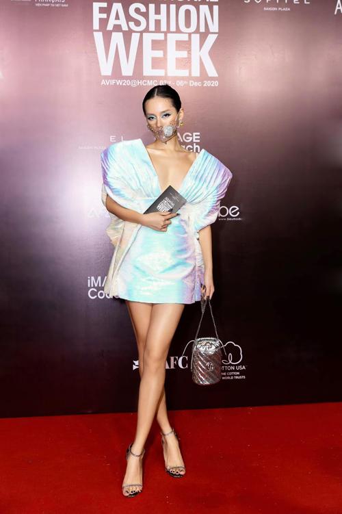 Khánh Linh luôn là fashionista gây ấn tượng mạnh mẽ bởi cách mix-match trang phục khi tham gia các sự kiện. Váy phối vải xếp ly đi kèm cầu vai độc đáo của Công Trí được cô mix cùng túi ánh bạc và mẫu khẩu trang nhựa trong đính đá.
