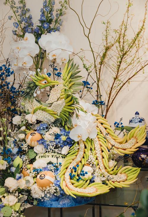 Tráp rồng - phượng được kết hoa, cắt tỉa thủ công. Đây là hai tráp lễ quen thuộc với người Hà Nội. Khi kết cùng hoa lan hồ điệp trắng, thanh liễu, cát tường xanh, nghệ nhân muốn tái hiện hình ảnh rồng - phượng cuộn mây, mang thông điệp về một cặp long-phụng hảo hợp, tứ kết đồng tâm.