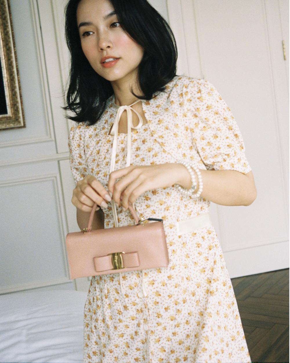 Thứ ba sẽ ngọt ngào và nữ tính hơn với váy họa tiết vintage và túi xách tay Viva màu hồng phấn. Tuy nhiên, Hà Trúc không chọn dáng túi thông thường mà tạo điểm nhấn với hình chữ nhật mini-size.