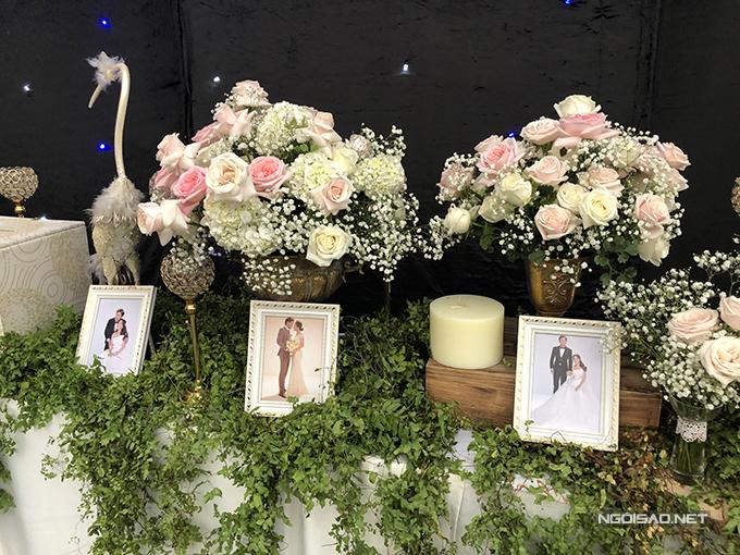 Không gian tiệc của uyên ương mang phong cách rustic. Bàn tiếp tân được trang trí với hoa hồng tươi, cẩm tú cầu và ảnh cưới của uyên ương.