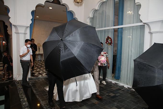 Cô dâu, chú rể được che kín bởi dù đen để Ảnh: Maison de Bil