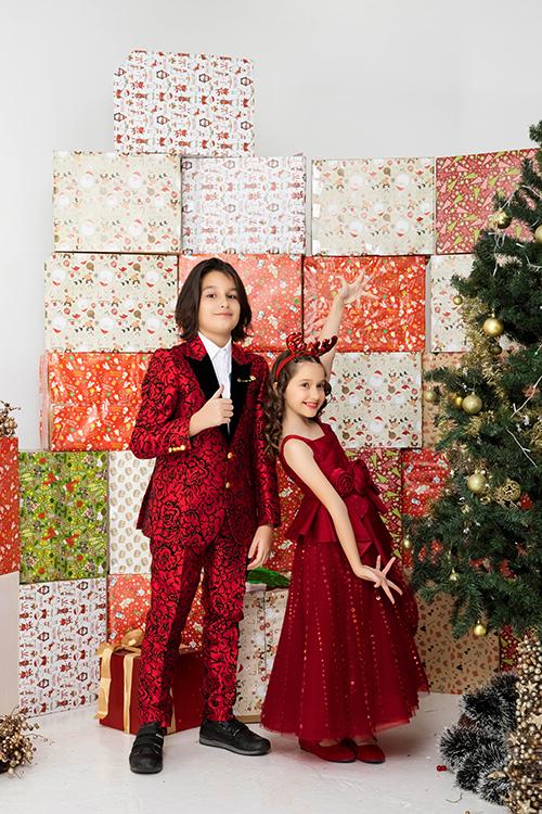 Suit dành cho các bé trai cũng được sử dụng tông đỏ đậm chất Giáng sinh nhưng đan xen hoạ tiết hoa văn cá tính bởi sắc đen.