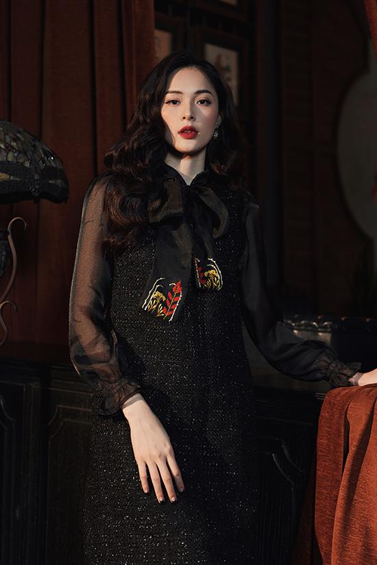 Với kiểu váy tương tự nhưng với màu đen, NTK Đặng Phương Linh tạo điểm nhấn tinh tế bằng chi tiết hoa lá thêu tay màu sắc ở nơ cổ.