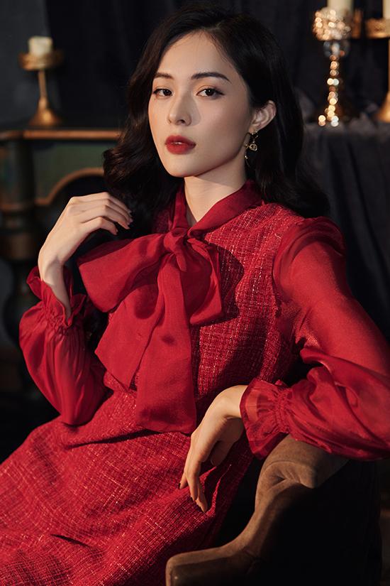 Chiếc váy suông chất liệu vải tweed trở nên nữ tính, mềm mại hơn với thiết kế nơ cổ và tay bồng may từ voan tơ mềm mại. Tông màu đỏ đun khiến làn da của Hạ Vi trông tươi sáng hơn kết hợp với kiểu dáng kín đáo, vừa đủ lịch sự để đi làm nhưng cũng vừa đủ nữ tính cho những buổi tiệc tối.