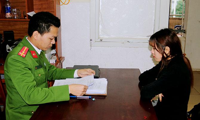 Nghi can Trang (góc phải) làm việc với cảnh sát. Ảnh: Hùng Lê