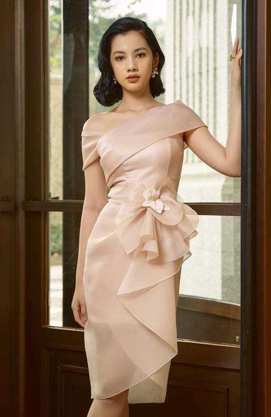 Váy trễ vai, xếp nếp kiểu bèo nhún phù hợp với tính cách dịu dàng của người đẹp. Cô để hai kiểu tóc ngắn và búi cao cổ điển, trang điểm nhẹ nhàng trông rất tự nhiên, cuốn hút.