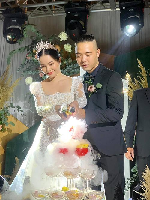 Thuỳ An thay váy cưới chính khi thực hiện nghi thức cưới trên sân khấu. Mẫu đầm thanh lịch, được làm từ ren Pháp, có đường xẻ khoe khéo đôi chân thon.