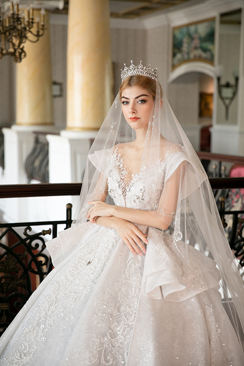 Mẫu váy cưới tiếp theo có hoạ tiết ren hoa văn kiểu Âu chạy dọc thân, giúp kéo dài chiều cao cơ thể của tân nương một cách tự nhiên. Phần tay áo xếp nếp giúp làm tăng vẻ quyền uy của cô dâu trong ngày cưới.
