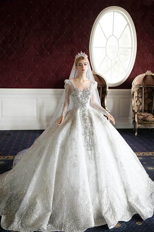 Chất liệu ren làm váy được nhập khẩu từ Pháp và được đính kết toàn bộ phần hoa văn, hoạ tiết lấy cảm hứng từ những hoạ tiết phù điêu cổ Châu Âu, mang đến hơi thở thời trang váy cưới cổ điển.