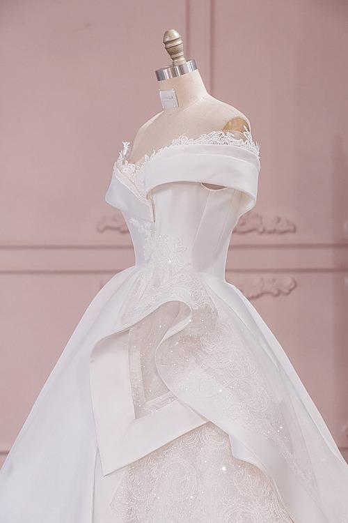 Ngoài ra, để khoe bờ vai thon gọn và thu hút mọi ánh nhìn, NTK Linh Nga đã thiết kế kiểu vai trễ cách điệu bởi ren Pháp, giúp xây dựng phong cách cổ điển, nhẹ nhàng cho nàng dâu.