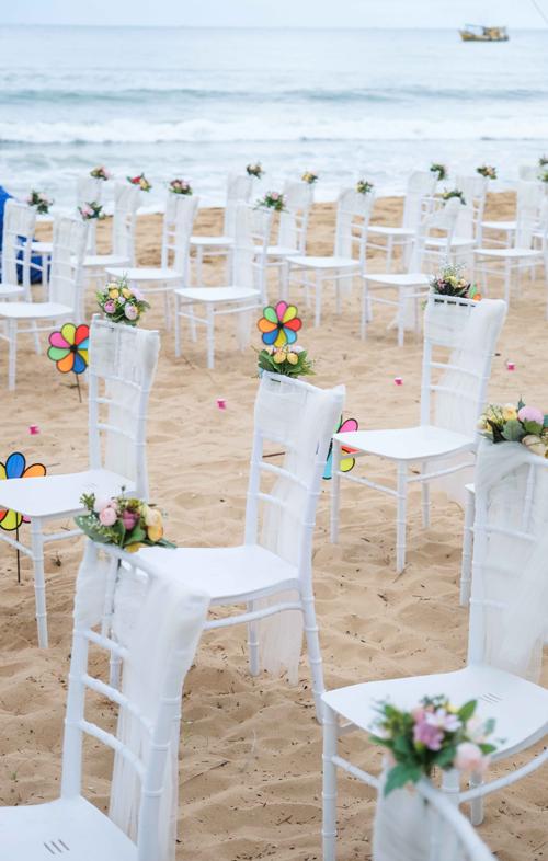 Nữ doanh nhân chọn lựa ghế Chiavari trắng được tô điểm với dải lụa cùng tông cho tiệc bãi biển.