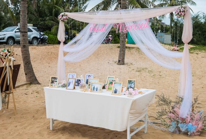Khu vực tiếp tân được bài trí với ảnh cưới của cặp vợ chồng. Tông màu chủ đạo của buổi tiệc là trắng - hồng và xanh.
