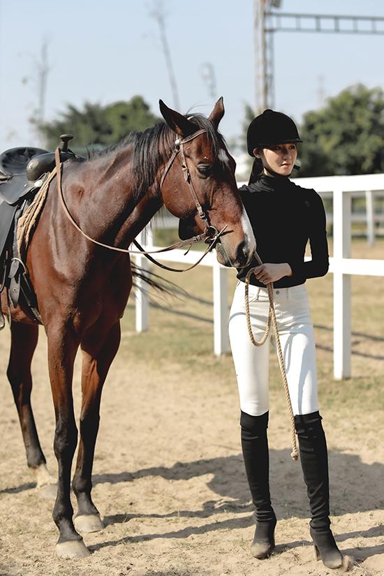 Phạm Lan Anh phối quần skinny trắng với áo len cao cổ và boot màu đối lập. Đây là trang phục thường được các quý cô phương Tây diện khi học cưỡi ngựa.