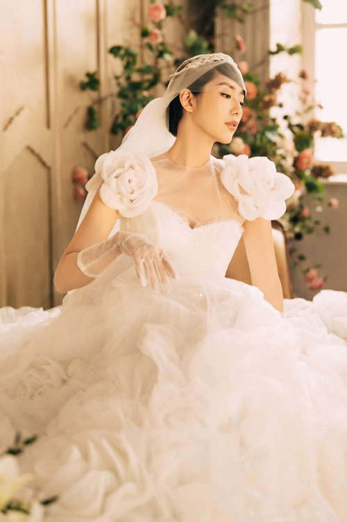 Chi tiết tay áo với hình ảnh hai bông hoa hồng bung nở rất được các nàng dâu yêu thích. Cổ váy đáp voan giúp định hình dáng váy và giữ nét thanh lịch cho nàng dâu.