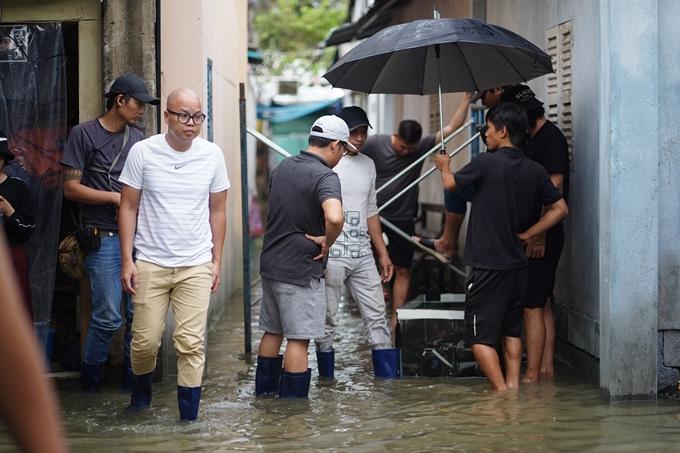 Đạo diễn Vũ Ngọc Đãng (áo trắng) lội nước chỉ đạo cảnh ngập nước trong phim Bố già.