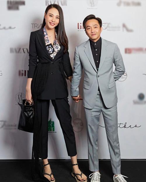 Cường Đôla và bà xã Đàm Thu Trang tay trong tay khi đến ủng hộ show thời trang tại TP HCM.