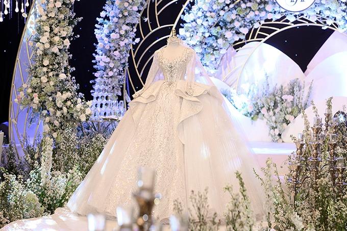 Trong ngày trọng đại, chú rể Xemesis tặng cô dâu của mình váy cưới chính có giá 1,2 triệu USD, tương đương 28 tỷ đồng. Mẫu đầm là tác phẩm của NTK Linh Nga, lấy cảm hứng từ hoạ tiết tân gothic (néo-gothique) trong kiến trúc của những lâu đài nguy nga của châu Âu. Thiết kế được tăng vẻ sang trọng nhờ đắp ren dệt pha lê Italy, nhấn nhá bởi 50.000 viên đá Swarovski ánh lấp lánh, nhập khẩu từ Áo. Các chi tiết trang trí cho bộ cánh đều theo hoạ tiết tân gothic đăng đối trên nền vải bắt sáng. Sự đắt giá của bộ cánh đến từ hơn 20 loại đá quý đính kết trên ngực áo, trên đó có 6 viên kim cương tự nhiên có khối lượng 20 carat. Tất cả các loại đá đều được đặt trực tiếp từ xưởng chế tác nổi tiếng của Pháp, đính kết thủ công bởi nghệ nhân trong vòng 20 giờ đồng hồ.