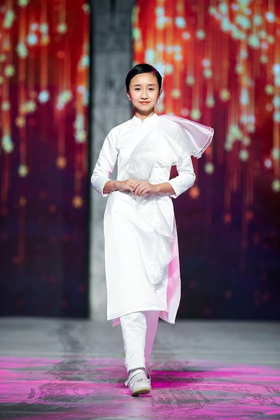 Với màu chủ đạo là trắng, những mẫu áo dài dành cho bé gái vẫn tạo được nét khác biệt với cách tạo điểm nhấn bằng  bèo nhún, hoa 3D...