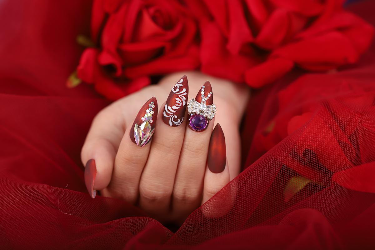 Bộ nail đỏ được Võ Hoàng Yến sử dụng trong show diễn thời trang nổi bật với các hoa văn màu trắng thanh lịch kèm chi tiết đính đá sang trọng. Ảnh: Hải Trần.