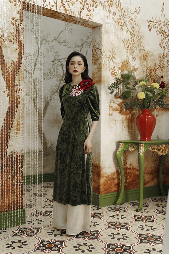 Áo dài nhung màu rêu tạo cảm giác trẻ trung, như được thổi một làn gió tươi mới nhờ những đóa hoa thêu đính trên vai áo, gợi cảm hứng về sức sống bung nở của muôn loài khi xuân về.