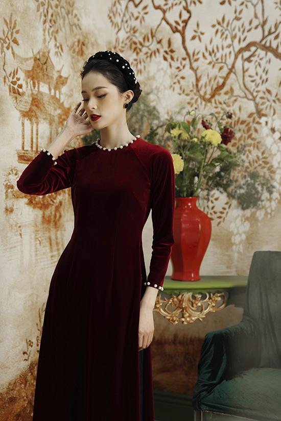 Áo dài nhung the đỏ ôm sát vừa mang đến vẻ ngoài nền nã, sang trọng vừa giúp Hạ Vi khéo léo khoe được vóc dáng cân đối. Những hạt ngọc trai to bản đỉnh ở cổ và tay áo trở thành điểm nhấn, khiến áo dài thêm thu hút ánh nhìn.