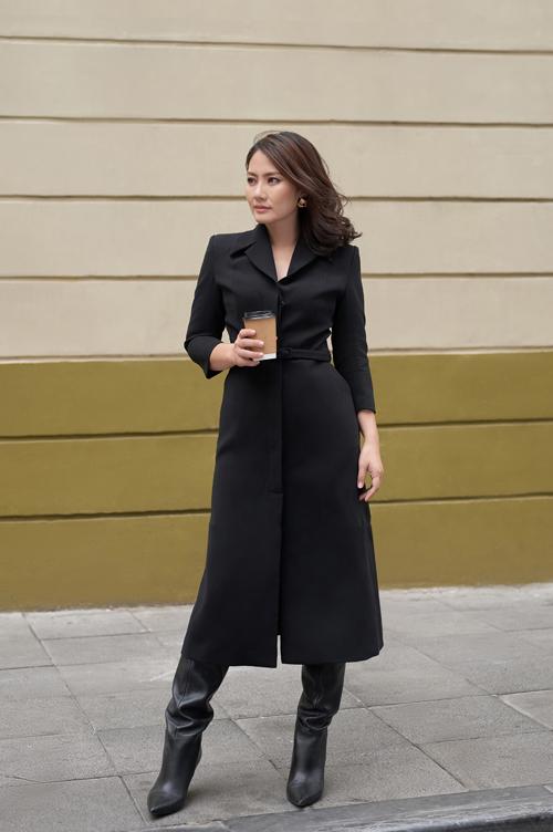 Nữ diễn viên đón tiết trời đông Hà Nội bằng set đồ màu đen với kiểu áo khoác coat dress dáng dài, cổ 2 ve mạnh mẽ kết hợp bốt da ngang gối ấm áp