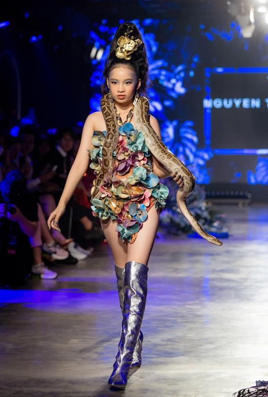 Lễ hội Thời trang Việt Nam Quốc tế diễn ra 4 ngày từ 25 đến 28/12 tại TP HCM quy tụ dàn mẫu đông đảo tham gia giới thiệu sưu tập của các nhà thiết kế nổi tiếng. Trong số đó, bé Bảo Hà được chú ý hơn cả vì là mẫu nhí hiếm hoi catwalk cùng các đàn chị tên tuổi.Bảo Hà khiến khán giả hồi hộp xen lẫn thích thú khi ra sàn runway với chú trăn gấm trên vai, mở màn sưu tập mang màu sắc nhiệt đới Khúc hòa ca Tropicana vùng châu Á của Nguyễn Tiến Truyển.