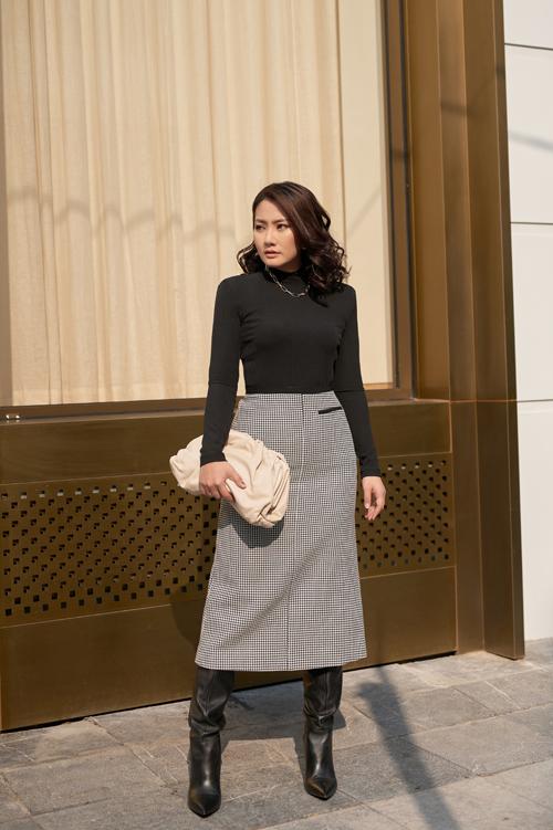 Ngọc Lan kết hợp áo len độn vai, chân váy kẻ đen trắng ,mix với dây chuyền mắt xích to bản là xu hướng của năm 2021.