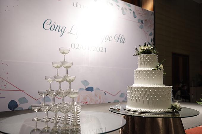 Bánh cưới cũng mang tông trắng, được điểm hạt mô phỏng viên ngọc trai.
