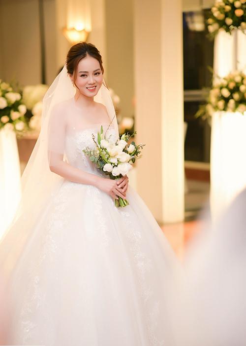 Mẫu váy chính của tiệc cưới được lấy cảm hứng từ áng mây trắng trên bầu trời. Chiếc váy dáng bồng công chúa với phần chân váy được làm từ 15 lớp voan và lụa siêu nhẹ, không cầu kỳ nặng nề như những chiếc váy công chúa thông thường.