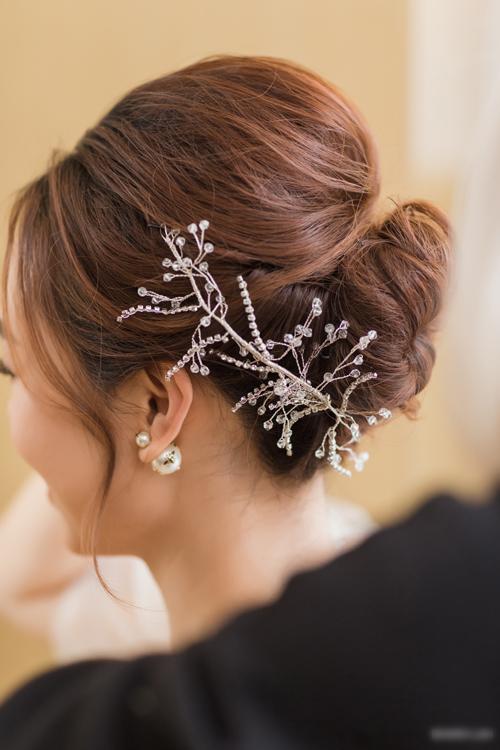 Tóc được búi gọn, tạo độ phồng bên trên và đính thêm bờm cườm, đá lấp lánh. Cô dâu kết hợp phụ kiện hoa tai ngọc trai để hoàn thiện vẻ ngoài.