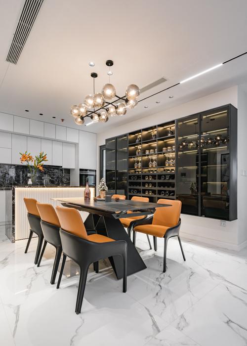 Bộ ghế bếp mang tông nóng giúp căn hộ với tông lạnh chủ đạo trở nên ấm áp hơn. Tủ rượu cũng có đèn vàng tạo điểm nhấn bắt mắt, mang đến sự sang trọng.