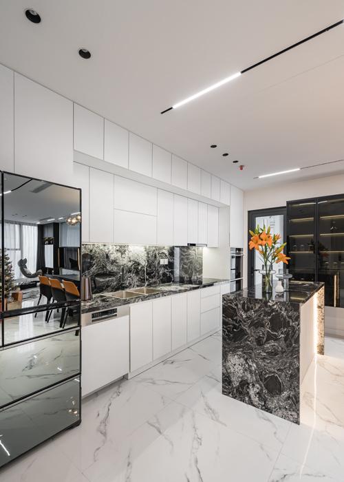 Căn bếp tối giản có các hệ tủ lớn tông trắng. Điểm nhấn thị giác ở đây là bàn đảo, mặt bếp ốp đá granite Black Forest.