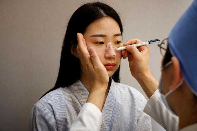 Bác sĩ tạo dáng mũi trước khi phẫu thuật cho một bệnh nhân tại một bệnh viện thẫm mỹ ở Seoul, Hàn Quốc hồi tháng 12/2020. Ảnh: Reuters.