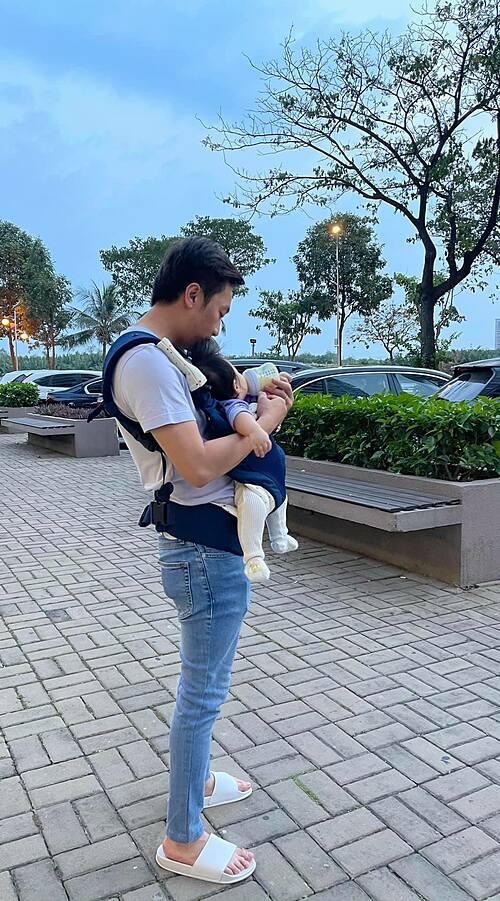 Cường Đôla đi dép lê, mặc giản dị và ra dáng ông bố bỉm sữa khi địu con đi dạo.