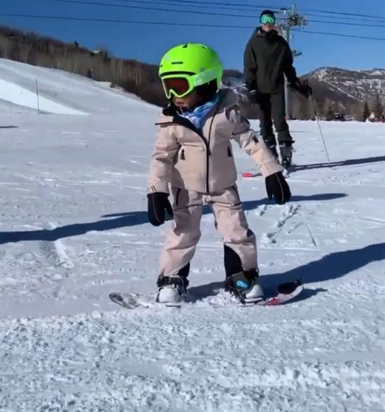 Stormi sành điệu trong bộ đồ trượt tuyết màu trắng và mũ bảo hiểm xanh. Cô bé đứng vững chãi trên chiếc ván trượt.